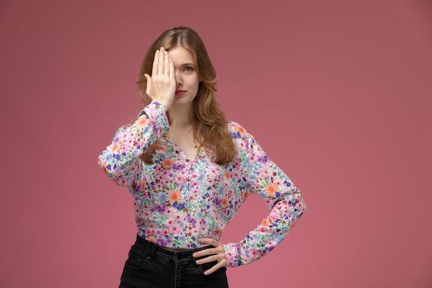 Vue de face jeune femme couvrant son œil droit avec sa main droite