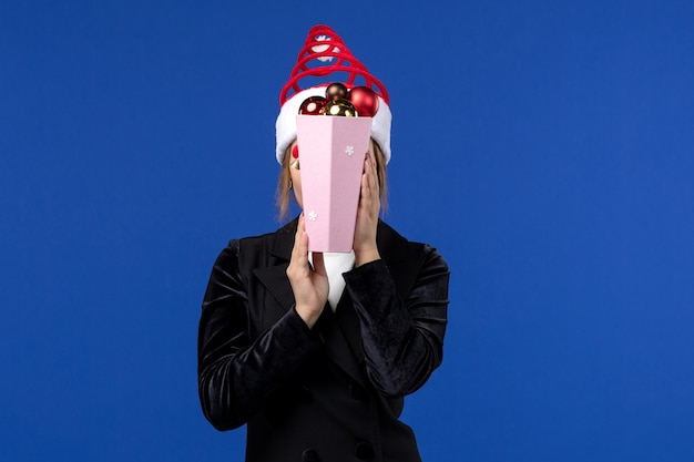Vue de face jeune femme couvrant son visage avec des jouets sur le mur bleu émotion vacances du nouvel an
