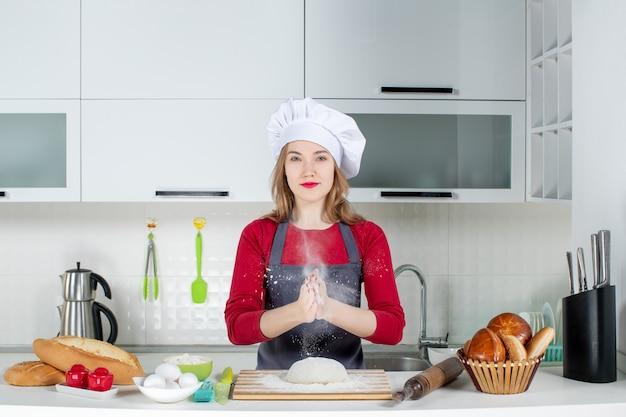Vue de face jeune femme cuisinier en chapeau de cuisinier et tablier frappant des mains avec de la farine dans la cuisine