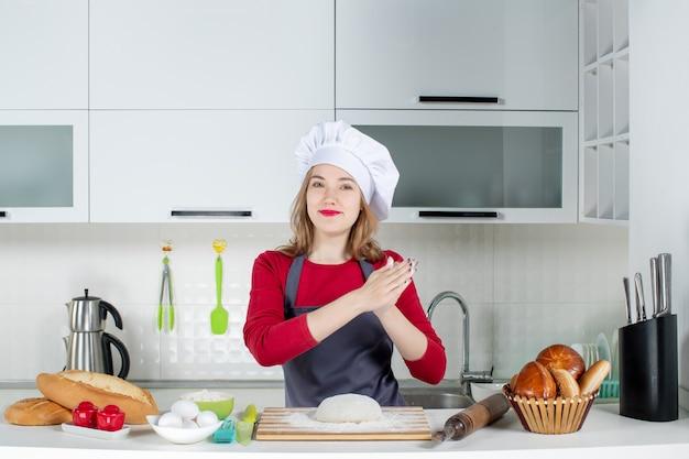 Vue de face jeune femme cuisinier en chapeau de cuisinier et tablier joignant les mains dans la cuisine