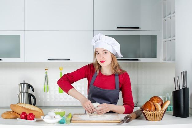 Vue de face jeune femme cuisinier en chapeau de cuisinier et tablier pétrir la pâte dans la cuisine