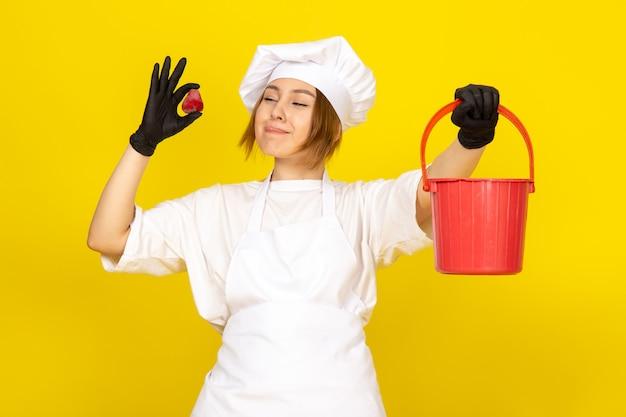 Une vue de face jeune femme cuisinier en costume de cuisinier blanc et bonnet blanc en gants noirs tenant panier rouge et fraise souriant sur le jaune