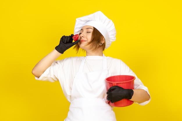 Une vue de face jeune femme cuisinier en costume de cuisinier blanc et bonnet blanc en gants noirs tenant panier rouge souriant sentant la fraise sur le jaune