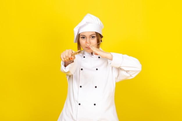 Une vue de face jeune femme cuisinier en costume de cuisinier blanc et bonnet blanc tenant un couteau menaçant sur le jaune