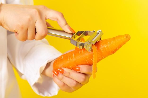 Une vue de face jeune femme cuisinier en costume de cuisinier blanc et bonnet blanc tenant et nettoyage carotte orange sur le jaune