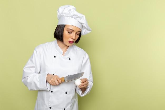 Une vue de face jeune femme cuisinier en costume de cuisinier blanc et chapeau cassant l'oeuf sur le mur vert