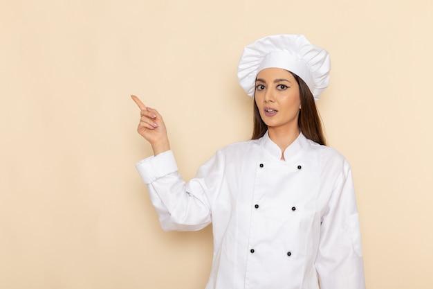 Vue de face de la jeune femme cuisinier en costume de cuisinier blanc levant son doigt sur un mur blanc clair