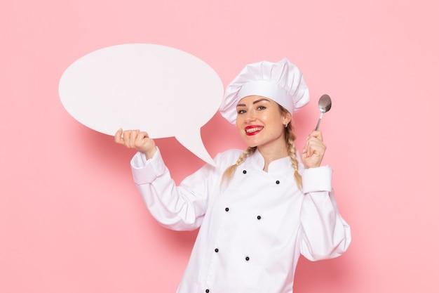 Vue de face jeune femme cuisinier en costume de cuisinier blanc tenant une pancarte blanche avec cuillère en argent sur l'espace rose cook