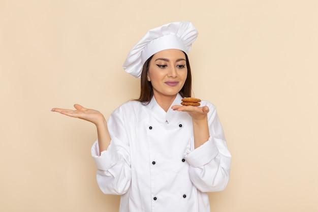 Vue de face de la jeune femme cuisinier en costume de cuisinier blanc tenant petit cookie sur mur blanc