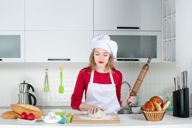 Vue de face jeune femme cuisinier pétrir la pâte sur une planche à découper tenant un rouleau à pâtisserie dans la cuisine