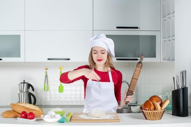 Vue de face jeune femme cuisinier saupoudrer de farine à la pâte sur une planche à découper dans la cuisine