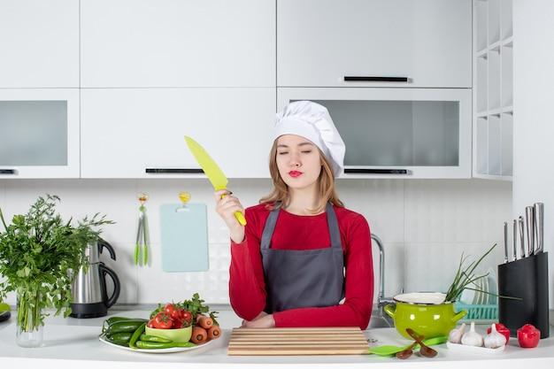 Vue de face jeune femme cuisinier en tablier tenant un couteau jaune