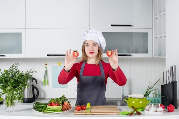Vue de face jeune femme cuisinier en tablier tenant des tomates coupées