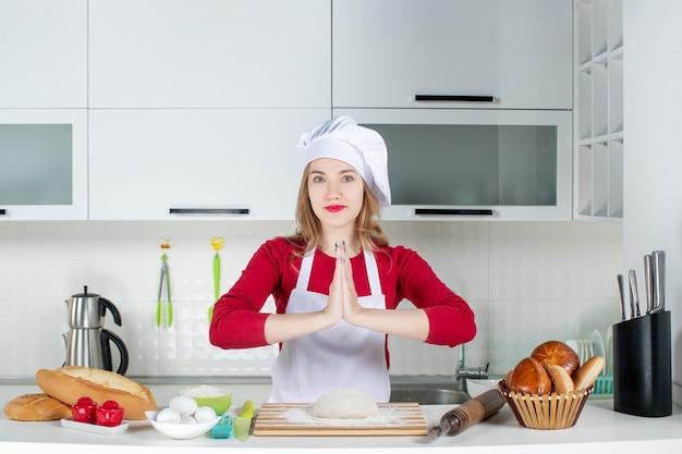 Vue de face jeune femme cuisinière en chapeau de cuisinier et tablier joignant ses mains dans la cuisine