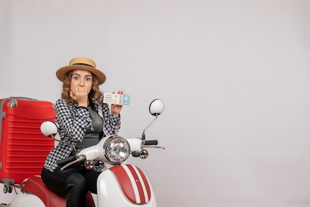 Vue de face jeune femme sur cyclomoteur brandissant un billet de voyage