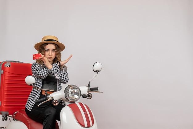 Vue de face jeune femme sur cyclomoteur holding card crossing hands
