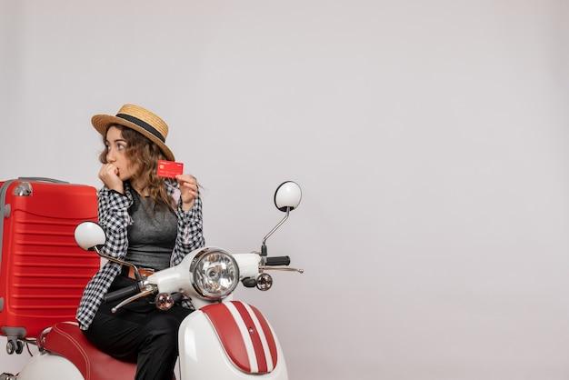 Vue de face jeune femme sur cyclomoteur holding card regardant à gauche