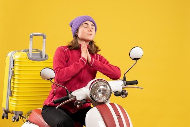 Vue de face jeune femme sur cyclomoteur joignant les mains et priant