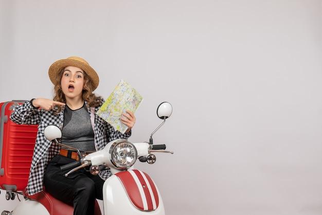 Vue de face jeune femme sur cyclomoteur pointant sur la carte