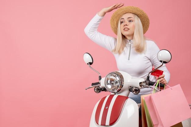Vue de face jeune femme sur cyclomoteur avec des sacs à provisions pressé