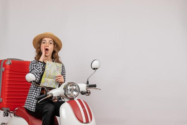 Vue de face jeune femme sur cyclomoteur tenant une carte appelant quelqu'un