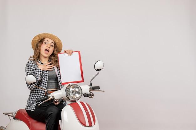 Vue de face jeune femme sur cyclomoteur tenant le presse-papiers rouge