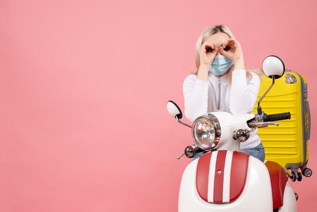 Vue de face jeune femme sur cyclomoteur avec valise jaune faisant des jumelles à main