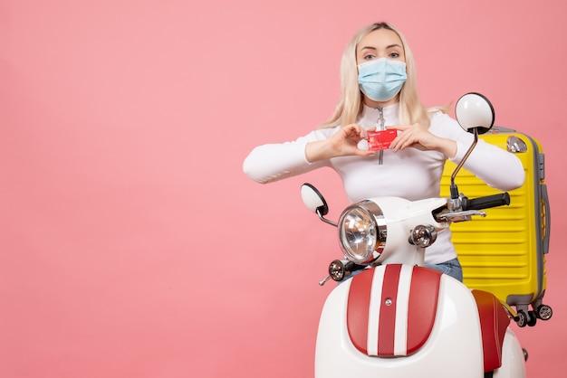 Vue de face jeune femme sur cyclomoteur avec valise jaune holding card