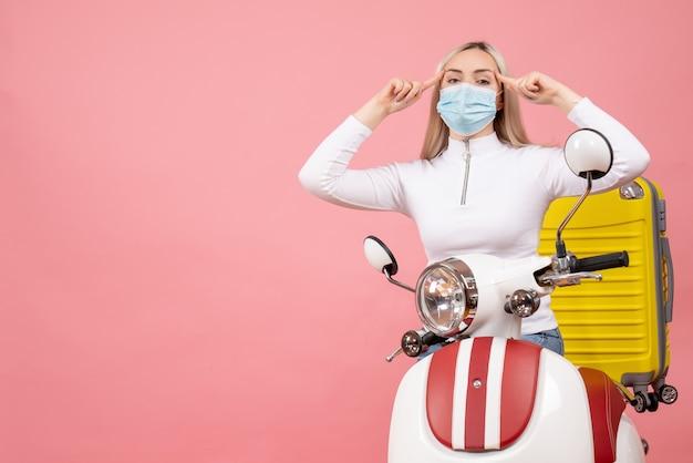 Vue de face jeune femme sur cyclomoteur avec valise jaune mettant les doigts sur sa tempe
