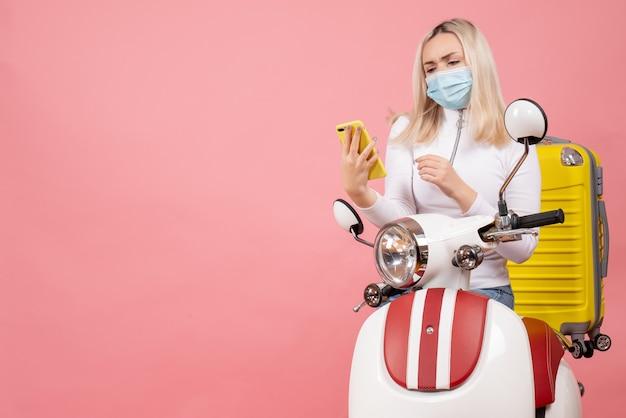 Vue de face jeune femme sur cyclomoteur avec valise jaune en regardant son téléphone