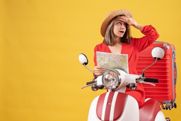 Vue de face jeune femme sur cyclomoteur avec valise rouge tenant une carte mettant la main sur son front