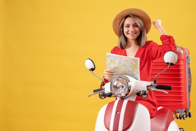 Vue de face jeune femme sur cyclomoteur avec valise rouge tenant une carte montrant le muscle du bras