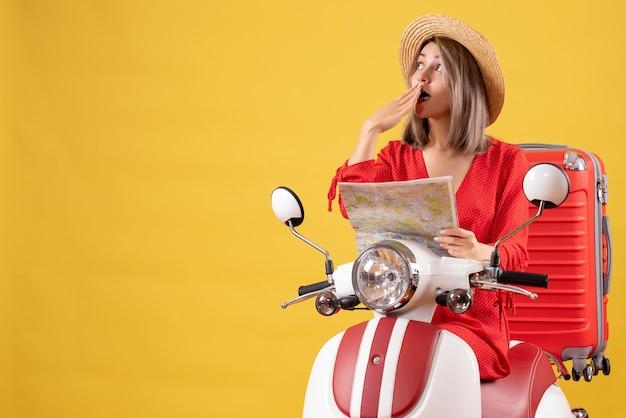 Vue de face jeune femme sur cyclomoteur avec valise rouge tenant une carte en pensant à quelque chose