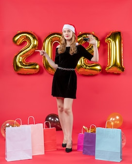 Vue de face jeune femme dans des sacs de robe noire sur des ballons au sol sur une photo de noël rouge