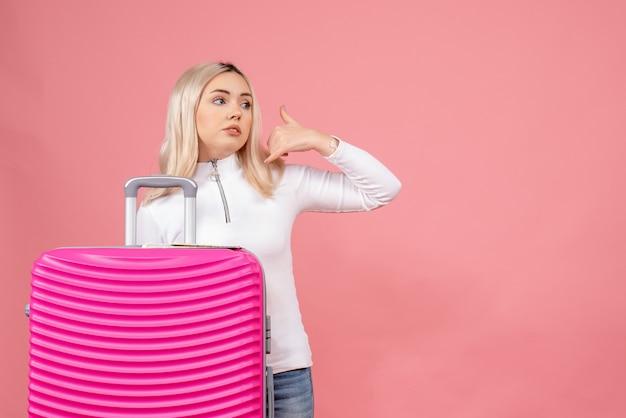 Vue de face, jeune femme, debout, derrière, valise rose, faire, appelez-moi, téléphone, geste