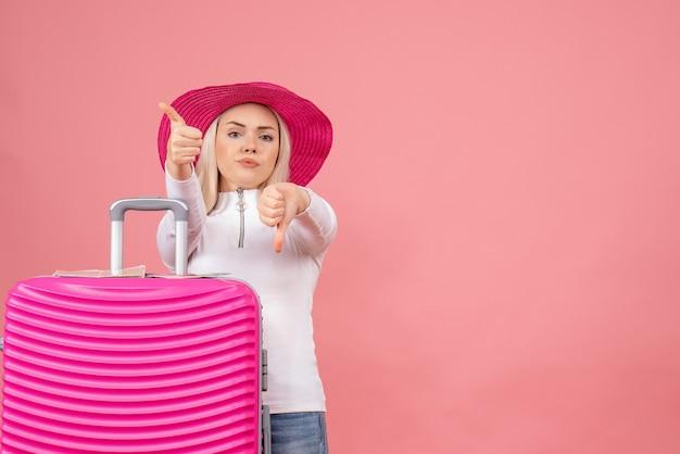 Vue de face, jeune femme, debout, derrière, valise rose, faire, pouces haut et bas, signes