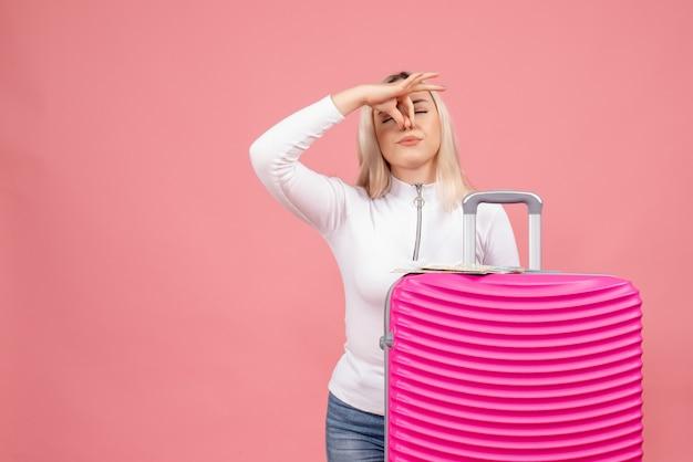 Vue de face jeune femme debout derrière valise rose tenant le nez