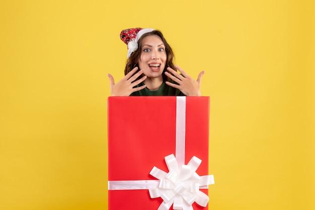 Vue de face de la jeune femme debout à l'intérieur de la boîte sur un mur jaune clair
