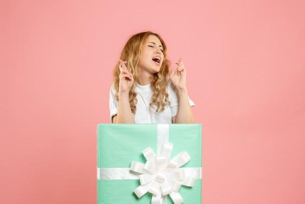 Vue de face jeune femme debout à l'intérieur de la boîte présente bleu en espérant