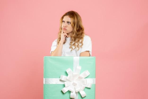 Vue de face jeune femme debout à l'intérieur de la boîte présente bleu