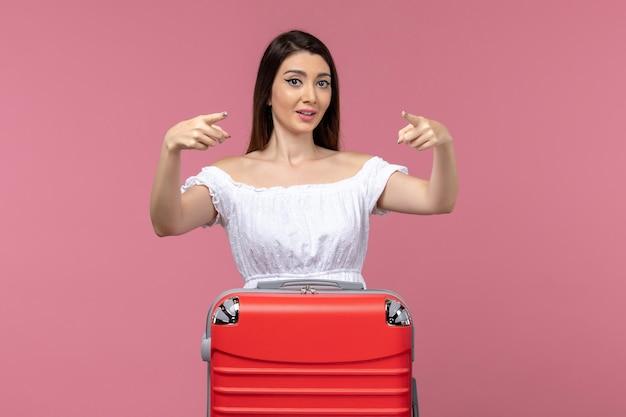 Vue de face jeune femme debout et préparation pour des vacances sur fond rose voyage voyage en mer femme à l'étranger vacances à l'étranger