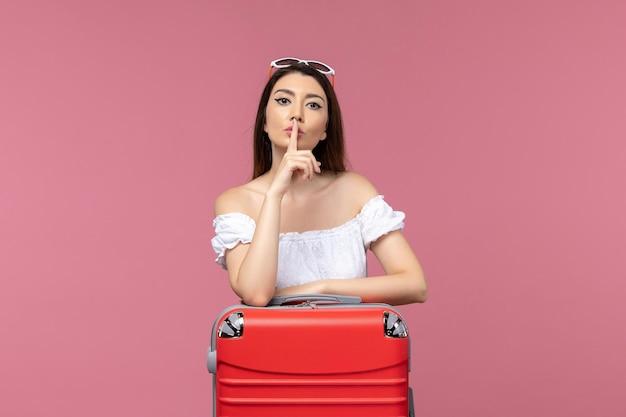 Vue de face jeune femme debout et se préparant pour des vacances sur fond rose clair voyage voyage en mer à l'étranger voyage féminin
