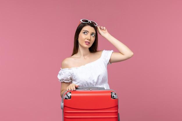 Vue de face jeune femme debout et se préparant pour des vacances sur le fond rose voyage voyage en mer à l'étranger voyage féminin