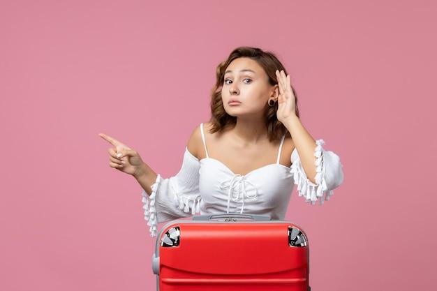 Vue de face d'une jeune femme écoutant attentivement avec un sac de vacances rouge sur un mur rose