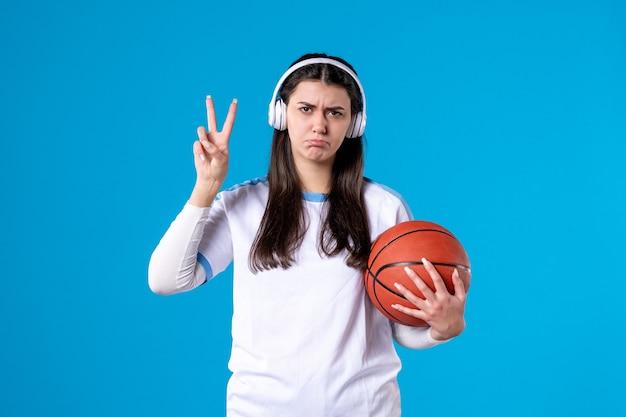 Vue de face jeune femme avec des écouteurs tenant le basket-ball sur le mur bleu
