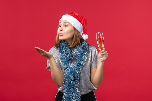 Vue de face jeune femme envoi de bisous sur le mur rouge fête de noël