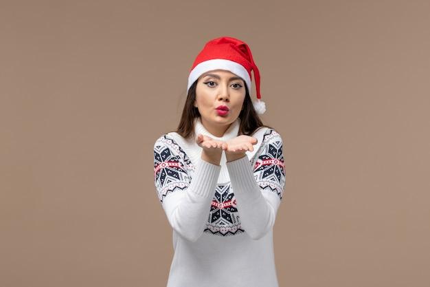 Vue de face jeune femme envoyant des baisers d'air sur fond brun émotion de noël nouvel an