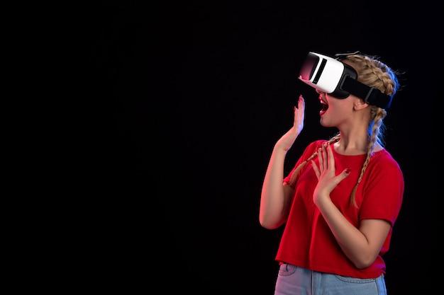 Vue de face d'une jeune femme excitée jouant au vr sur fond noir