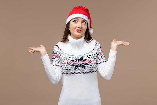 Vue de face jeune femme avec expression de rêve sur fond marron émotion noël nouvel an