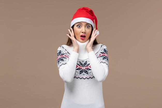 Vue de face jeune femme avec expression surprise sur fond marron émotion noël nouvel an